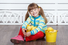 Little cute girl with lemons in two yellow buckets Stock Images