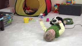 Little cute girl lie on white carpet between toy in her room. 4K stock footage