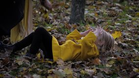 Little cute girl lies on an autumn meadow in beautiful park while her mom throws leaves in fall season, family fun