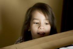 Little cute girl looking above bookshelf Stock Image