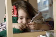 Little cute girl  looking above bookshelf. Royalty Free Stock Photo