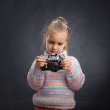 Little cute girl looks photos at the camera Royalty Free Stock Image