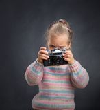 Little cute girl looks photos at the camera Royalty Free Stock Images