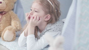 Little cute girl lying on the floor, Teddy bear soft about girls. stock footage
