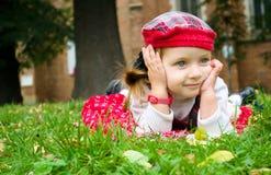Little girl lying on the grass. Little cute girl is lying on the grass at the park Royalty Free Stock Photography