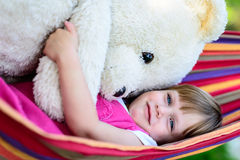 Little cute girl lying on hammock with large teddy bear Royalty Free Stock Photos