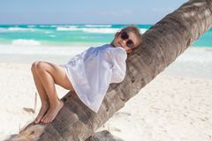 Little cute girl lying on palm tree at the perfect Royalty Free Stock Image