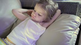 Little cute girl lying on sofa and playing tablet. Little cute girl lying on sofa and playing with tablet stock footage