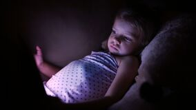 Little cute girl lying on sofa and playing tablet in full darkness. Little cute girl lying on sofa in full darkness and playing with tablet stock footage