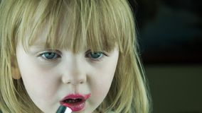 The little cute girl makes up lips with red lipstick stock video footage
