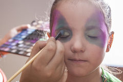 Little cute girl making facepaint before halloween party Stock Photography