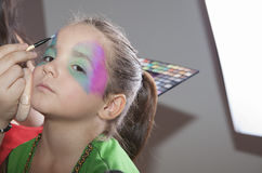 Little cute girl making facepaint before halloween party Royalty Free Stock Images