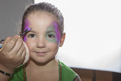 Little cute girl making facepaint before halloween party Stock Images