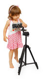 A little cute girl making making a shot with camera on tripod Royalty Free Stock Photos