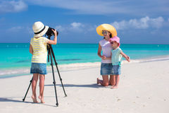 Little cute girl making photo of her family at tropical beach Stock Photo