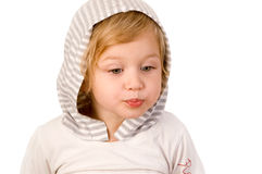 Little cute girl making a serious face. Close-up on white background Royalty Free Stock Photo