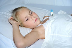 Little cute girl measures the temperature. On a white background on bed Stock Images