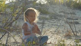 Little girl meditates at desert. Child sitting on the sand at sunset warm. Little cute girl meditates at desert. Child sitting on the sand at sunset warm light stock footage