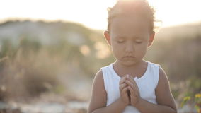 Little cute girl meditates outdoor at sunset with beautiful natural light