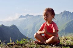 Little cute girl meditating on top of mountain. Portrait of child meditating in lotus pose Stock Images