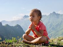 Little cute girl meditating on top of mountain. Portrait of child meditating in lotus pose Royalty Free Stock Photo