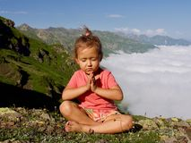 Little cute girl meditating on top of mountain. Portrait of child meditating in lotus pose higher than clouds Stock Photo