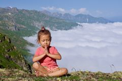 Little cute girl meditating on top of mountain. Portrait of child meditating in lotus pose higher than clouds Stock Photography