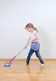Little cute girl mopping floor. Little cute girl mopping floor at home Royalty Free Stock Photography