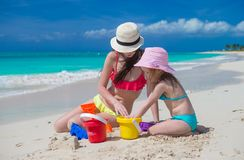 Little cute girl and mother building sandcastle at Stock Images