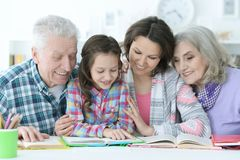 Little cute girl with mother and grandparents  studying Stock Photography