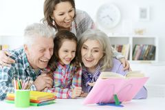 Little cute girl with mother and grandparents  studying Royalty Free Stock Image