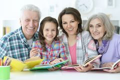 Little cute girl with mother and grandparents  studying Royalty Free Stock Photo