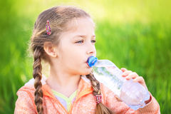 Little cute girl on the nature drinks water Stock Images