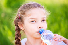 Little cute girl on the nature drinks water Royalty Free Stock Photo