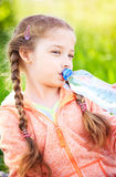 Little cute girl on the nature drinks water Royalty Free Stock Photography