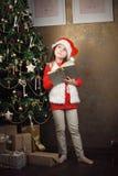 little cute girl near christmas tree holding book Stock Photo