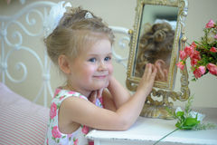 Little cute girl next to the mirror Stock Images