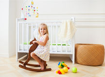 Little cute girl in nursery room. With basket, toys and wooden horse stock images