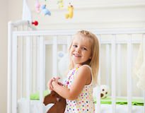 Little cute girl in nursery room. With toys and wooden horse royalty free stock image