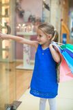 Little cute girl with packages in a large shopping Stock Photo
