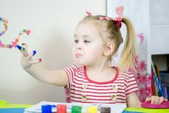Little cute girl paints with fingers. Cute girl shows dissapointment and sad emotions due to covered with paint hands and fingers Royalty Free Stock Images