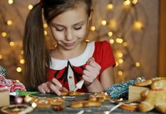 Free Little Cute Girl Paints Traditional Gingerbread Man. Royalty Free Stock Photos - 168070748