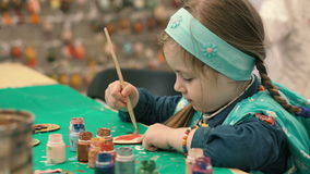 Little, cute girl paints the wooden figure stock footage