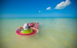 Little cute girl on pink air-bed in Caribbean sea Royalty Free Stock Images