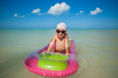 Little cute girl on pink air-bed in Caribbean sea Royalty Free Stock Photography