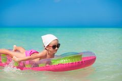 Little cute girl on pink air-bed in warm sea Stock Image