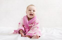 Little cute girl in pink bathrobe on white background. Little cute newborn girl in pink bathrobe laughing on white background, copy space royalty free stock photography