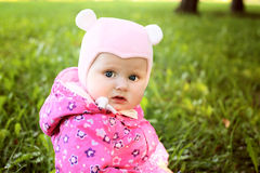 Little cute girl in pink coat in autmn park Stock Images