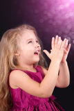 Little cute girl in a pink dress on a black background Stock Images