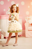 Little cute girl in a pink dress drinks tea with sweets in the c Royalty Free Stock Photos